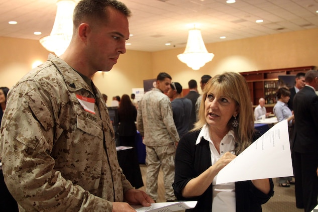 Terry Coulson speaks to Josh Lasure about available careers during the Hiring our Heroes job fair held at the Pacific Views Event Center here Sept. 19. The event was open to active duty, veterans, guard, reserve, and family members. Coulson is a human resources business partner at Granite construction.