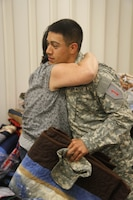After receiving a quilt made by volunteers during his recent deployment to Eastern Afghanistan, Spc. Jake Herrera, an infantryman of Co. D, 1st Bn., 28th Inf. Regt., 4th IBCT, 1st Inf. Div., receives a hug from Gina Flikkie, the organizer of the quilt drive. Flikkie organized over 30 volunteers; together the group quilted 90 blankets, one for every Soldier in the company. (U.S. Army photo by Sgt. Scott Lamberson, 4th IBCT PAO.)