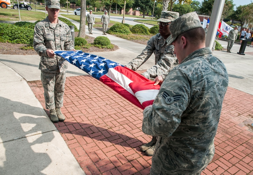 (Left to right) Airman 1st Class Matthew Lewis, Airman 1st Class Antwon Vaughn, and Senior Airman Tyler Vaughn, all members of the Joint Base Charleston Honor Guard fold the American flag during the Prisoner of War/Missing in Action retreat ceremony Sept. 23, 2013, at JB Charleston – Air Base, S.C. The ceremony included a 21-gun salute by the Honor Guard, a wreath-laying and bagpipe music in recognition of captured and missing U.S. servicemembers. (U.S. Air Force photo/Senior Airman Ashlee Galloway)