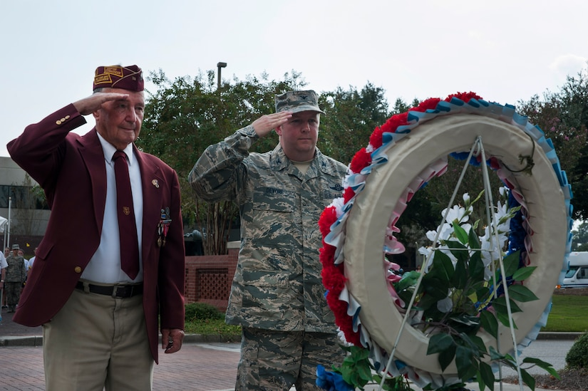 Reggie Salisbury, a U.S. Army infantry veteran, D-Day survivor and World War II prisoner of war, and Col. Jeff DeVore, Joint Base Charleston commander, salute after laying a wreath during the Prisoner of War/Missing in Action retreat ceremony Sept. 23, 2013, at JB Charleston – Air Base, S.C.  (U.S. Air Force photo/Senior Airman Ashlee Galloway)