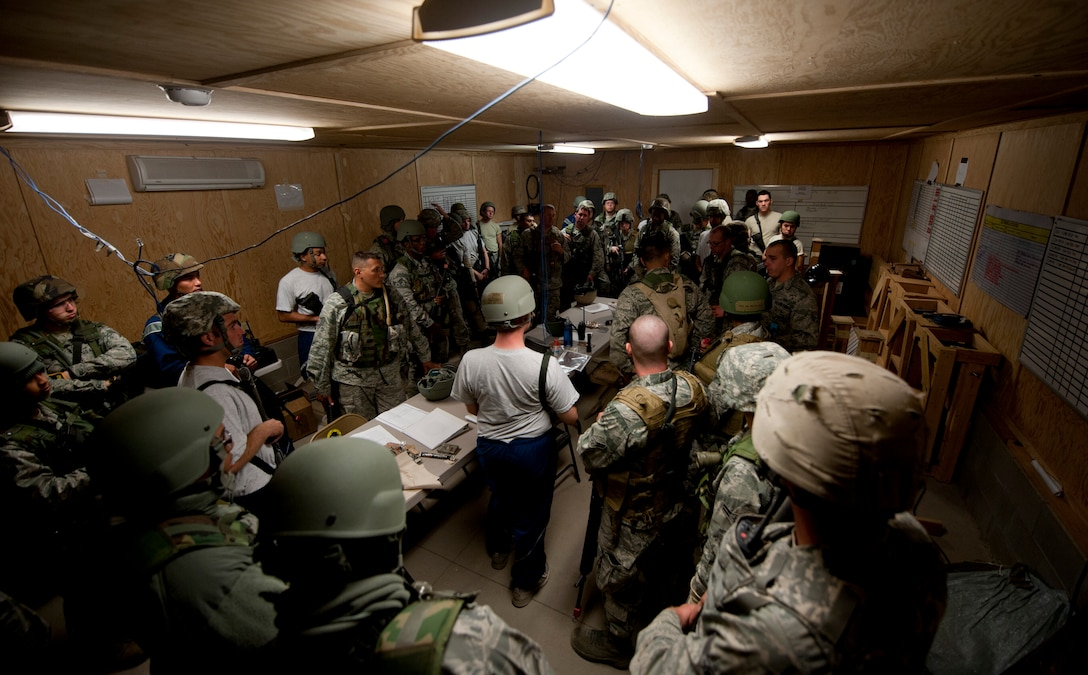 U.S. Air Force Airmen from the 726th Air Control Squadron gather at the mobile operating air base command post Sept. 17, 2013, at Mountain Home Air Force Base, Idaho. Airmen from the 726th ACS discussed how an exercise scenario played out during an after-action review. Understanding what was done incorrectly enables them to fix those problems, promoting success in future exercise scenarios or future deployments. (U.S. Air Force photo by Airman 1st Class Brittany A. Chase/Released)