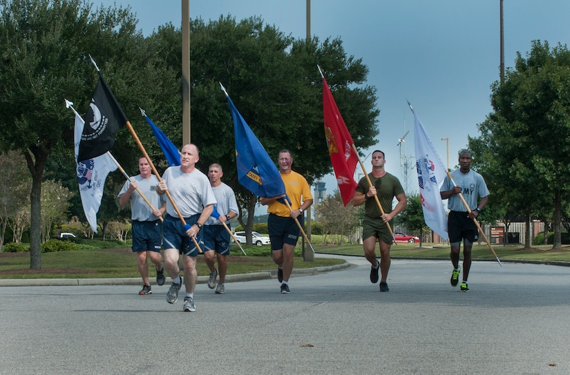 Members from each military branch run with their respective service flags to the Joint Base Charleston – Air Base parade grounds for the start of the Prisoner of War/Missing in Action Retreat ceremony Sept. 20, 2013, at JB Charleston, S.C. Teams from various joint base units took part in a vigil run around the base track, carrying the POW/MIA flag around the track non-stop for 24 hours.  (U.S. Air Force photo/Senior Airman Ashlee Galloway)