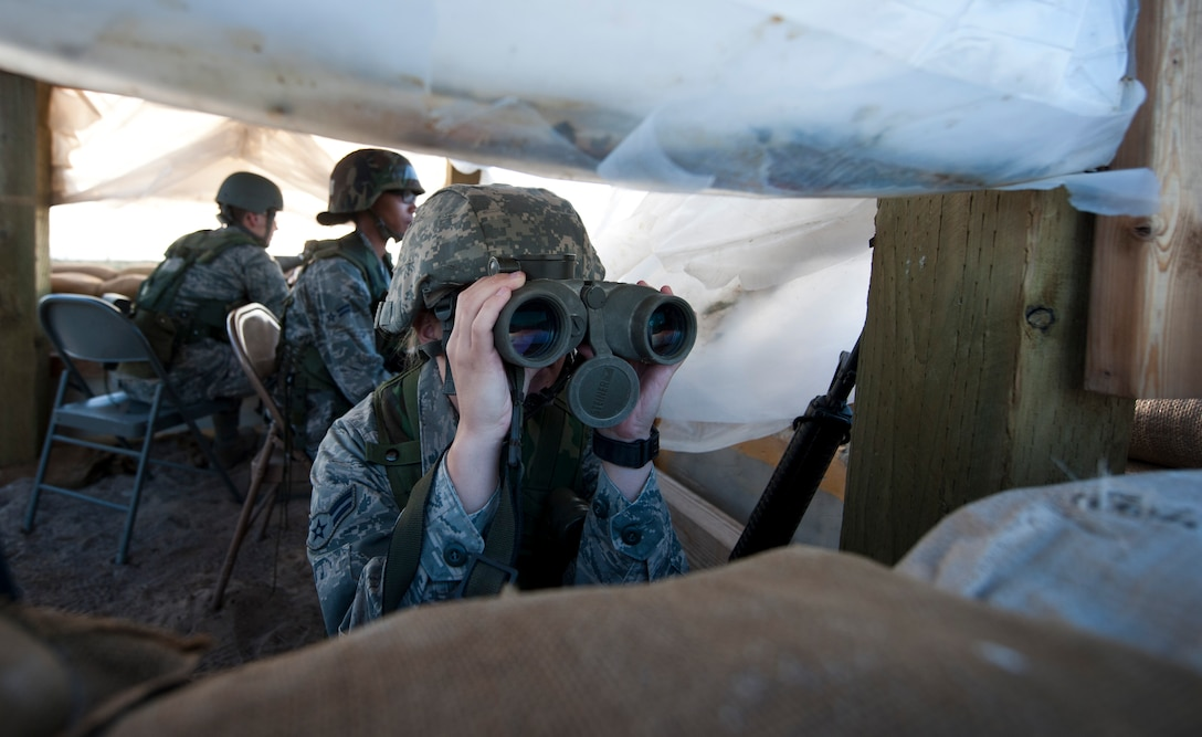U.S. Air Force Airman 1st Class Courtney McFerrin, 726th Air Control Squadron command control battle management operations apprentice, looks through binoculars in a defensive fighting position Sept. 18, 2013, at Mountain Home Air Force Base, Idaho. Vigilance is a key component when providing base security. Airmen from the 726th ACS were given multiple scenarios to test their abilities in safe-guarding wingmen along with Air Force assets. (U.S. Air Force photo by Airman 1st Class Brittany A. Chase/Released)