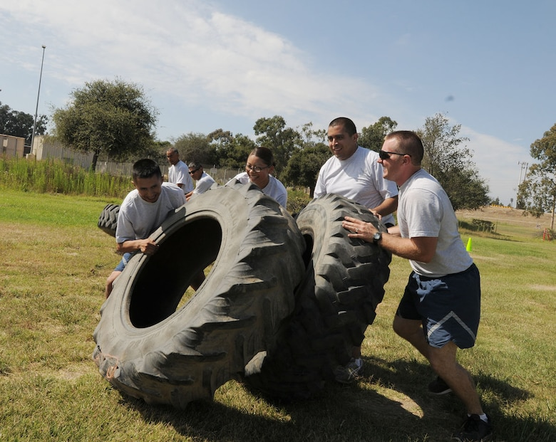 """Senior Airmen Mario Lopez-Casas, Senior Airmen  Betsaida Castellanos, Senior Airmen Ellis Garcia and   Staff Sgt. Jeff Toyne members of the 146th Civil Engineers """"trade paint"""" as they approach the finish line in the tire-flipping race during their PT session Sunday of August UTA. CE finds different ways each month to accomplish fitness training, promote a healthy lifestyle and have fun while they are doing it. Air National Guard photo by Master Sgt. Dave Buttner"""