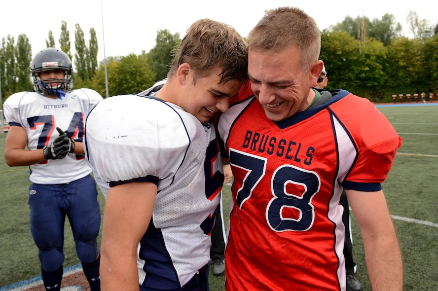 SPANGDAHLEM AIR BASE, Germany – U.S. Air Force Master Sgt. Scott Love, 52nd Equipment Maintenance Squadron NCO in charge of armorment from Pensacola, Fla., surprises his son, Kenny, at his football game against the International School of Brussels Sept. 21, 2013. Love and another Airman both surprised their sons by dressing up in the opposing team's football gear and acted as the team captains. A referee called a time-out after the third quarter when the fathers met with their sons. (U.S. Air Force photo by Airman 1st Class Kyle Gese/Released)