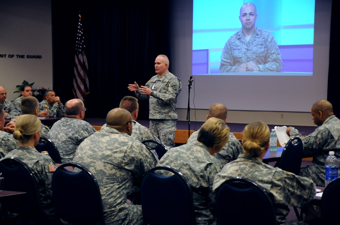 LITTLE ROCK, Ark. - Army COL Timothy Keasling, commandant of the National Guard's LaVern E. Weber Professional Education Center, gives an overview here, Sept. 16, 2013, to about 50 Army National Guard Soldiers during a live HD broadcast of U.S. Air Force Maj. Gabe Johnson, deputy commander of the I.G. Brown Training and Education Center (on screen). Johnson taught a professional development seminar about Personal Accountability from the I.G. Brown Training and Education Center in Tennessee. (U.S. Army National Guard courtesy photo/Released)