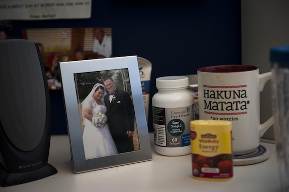 A picture of Heath Johnson and his wife, Mariceli Santiago, sits on his desk at work, along with vitamins. Johnson has lost 91 lbs since Feb. 25, 2013. Johnson is the Air Force Personnel Organization Division chief. (U.S. Air Force photo/Staff Sgt. David Salanitri)
