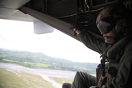 Sgt. Devon Morris observes a landing zone from an MV-22B Osprey at Crow Valley, Capas, Tarlac, Republic of the Philippines, Sept. 17 while on a site-survey mission during Amphibious Landing Exercise 2014. The recurrence of PHIBLEX, now in its 30th year, demonstrates the U.S. and Republic of the Philippines' commitment to mutual security and their long-time partnership. Morris is a crew chief with Marine Medium Tiltrotor Squadron 166, part of the 13th Marine Expeditionary Unit's aviation combat element.