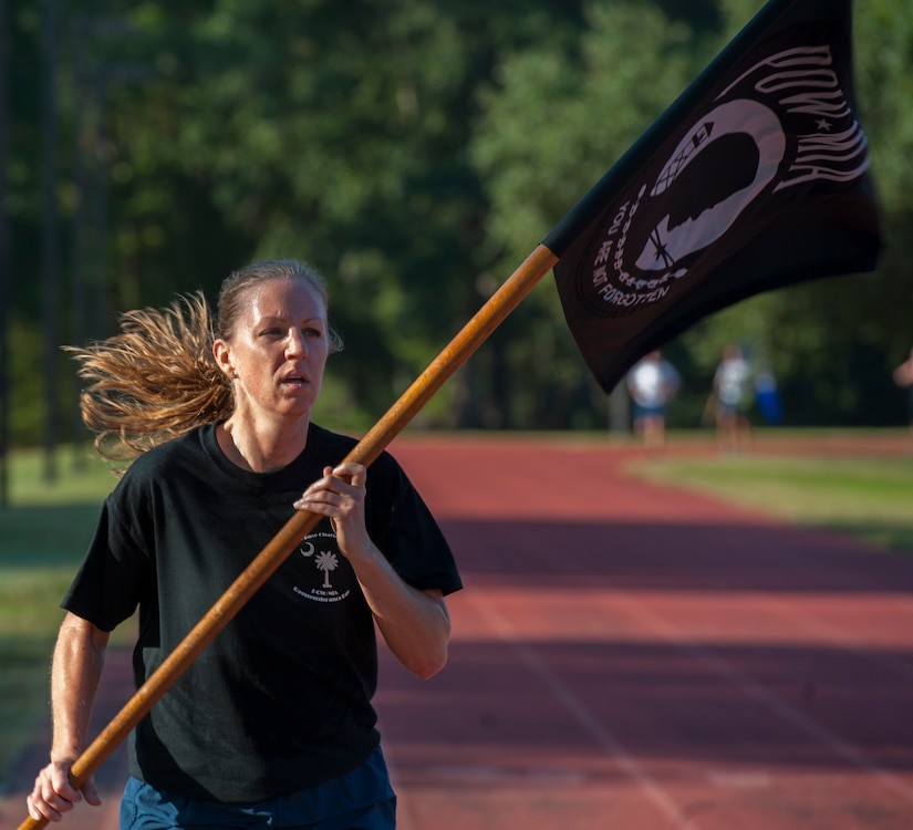 Tech. Sgt. Kristen Dierkhising, 315th Airlift Wing recruiter, runs with the POW-MIA flag during the POW/MIA Run Sept. 20, 2013, at Joint Base Charleston – Air Base, S.C. Different units from the joint base carried the flag in 30-minute increments from 3:30 p.m. Sept. 19 to 3:30 p.m. Sept. 20 in honor of all POWs and MIAs. Over 660 runners participated in the vigil and logged nearly 2,000 miles. (U.S. Air Force photo/ Airman 1st Class Chacarra Neal)