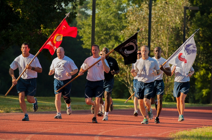 Airmen are seen running during the POW/MIA Run Sept. 20, 2013, at Joint Base Charleston – Air Base, S.C. Different units from the joint base carried the flag in 30-minute increments from 3:30 p.m. Sept. 19 to 3:30 p.m. Sept. 20 in honor of all POWs and MIAs. Over 660 runners participated in the vigil and logged nearly 2,000 miles. (U.S. Air Force photo/ Airman 1st Class Chacarra Neal)