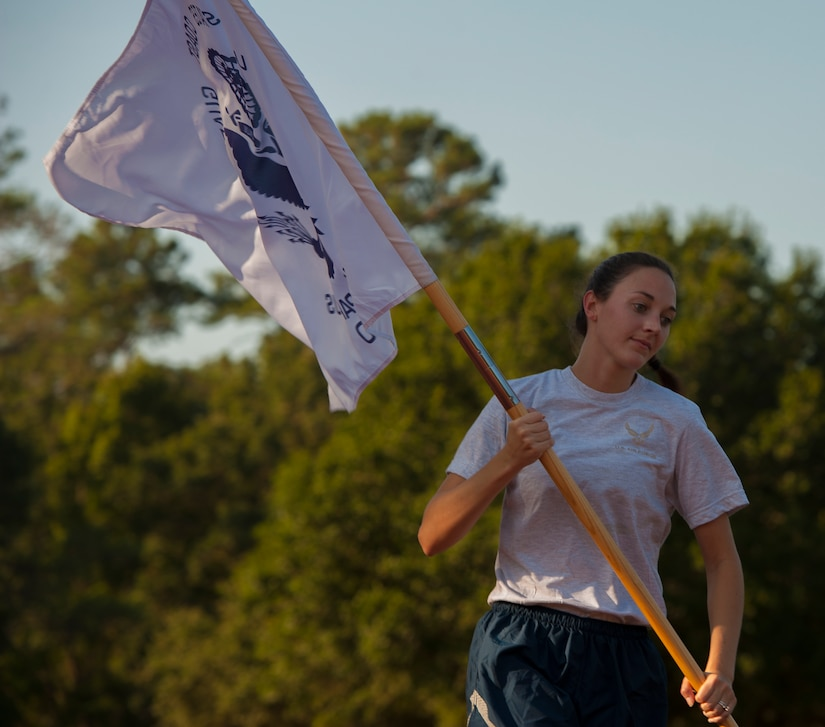 Capt. Rachel Rogalski, 315th Air Expeditionary Squadron flight nurse runs with a flag during the POW/MIA Run Sept. 20, 2013, at Joint Base Charleston – Air Base, S.C. Different units from the joint base carried the flag in 30-minute increments from 3:30 p.m. Sept. 19 to 3:30 p.m. Sept. 20 in honor of all POWs and MIAs. Over 660 runners participated in the vigil and logged nearly 2,000 miles. (U.S. Air Force photo/ Airman 1st Class Chacarra Neal)