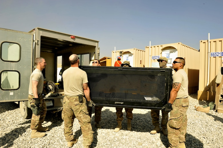 Airmen assigned to the 455th Expeditionary Communications Squadron unload a computer tower on Bagram Airfield, Afghanistan. The supplies will be used to build a communications equipment room and other systems. The Airmen spent three days setting up communication capability for future Jordanian coalition partners here.