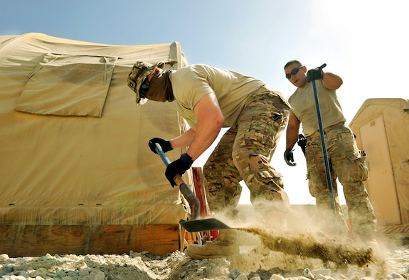 Capt. Wesley Parker, 455th Expeditionary Communications Squadron, operations flight commander, excavates trenches to hold conduit on Bagram Airfield, Afghanistan. The conduit will protect the fiber and copper cable running underground to the tents. He is deployed from Tinker Air Force Base, Okla., and is a native of Humble, Texas.