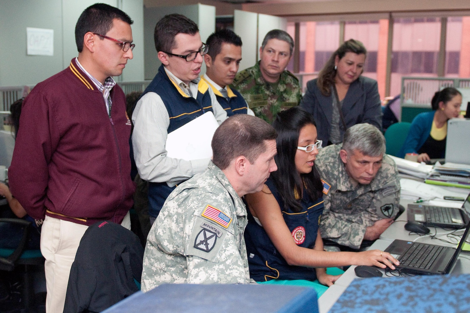 Members of the South Carolina National Guard visit the Colombia emergency services (UNGRD) office to see their programs in action. UNGRD staff shows SCNG staff how their system works with Google-based programs Sept. 13, 2013.