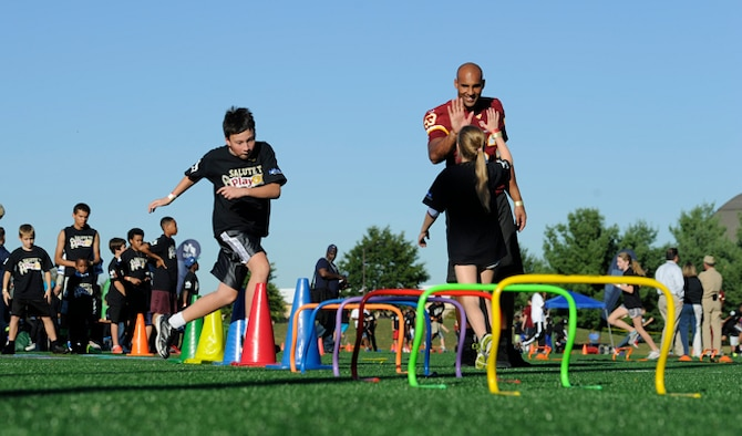 Washington Redskins linebacker Bryan Kehl high-fives a young girl during the Salute to Play 60 Military Challenge Sept. 24, 2013, at Joint Base Andrews, Md. The initiative is part of the National Football League's larger Play 60 campaign, which is designed to encourage kids to be active for 60 minutes a day to help reverse the trend of childhood obesity.
