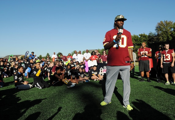 Washington Redskins quarterback Robert Griffin III speaks to the children about his personal connection with the military during the Salute to Play 60 Military Challenge Sept. 24, 2013, at Joint Base Andrews, Md. The son of Army parents, Griffin is familiar with the military lifestyle. The initiative is part of the National Football League's larger Play 60 campaign, which is designed to encourage kids to be active for 60 minutes a day to help reverse the trend of childhood obesity.