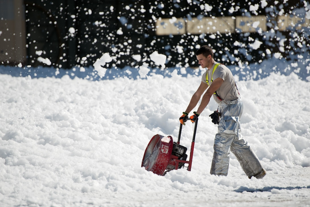 Senior Airman Allen Stoddard, 60th Civil Engineer Squadron, blows a small sea of fire retardant foam that was unintentionally released in an aircraft hangar at Travis Air Force Base, Calif.,  Sept. 24, 2013. The non-hazardous foam is similar to dish soap, which eventually dissolved into liquid, which was helped by high winds. The 60th Air Mobility Wing fire fighters helped control the dispersion  by using powerful fans and covering drains. No people or aircraft were harmed in the incident. (U.S. Air Force photo/Ken Wright)