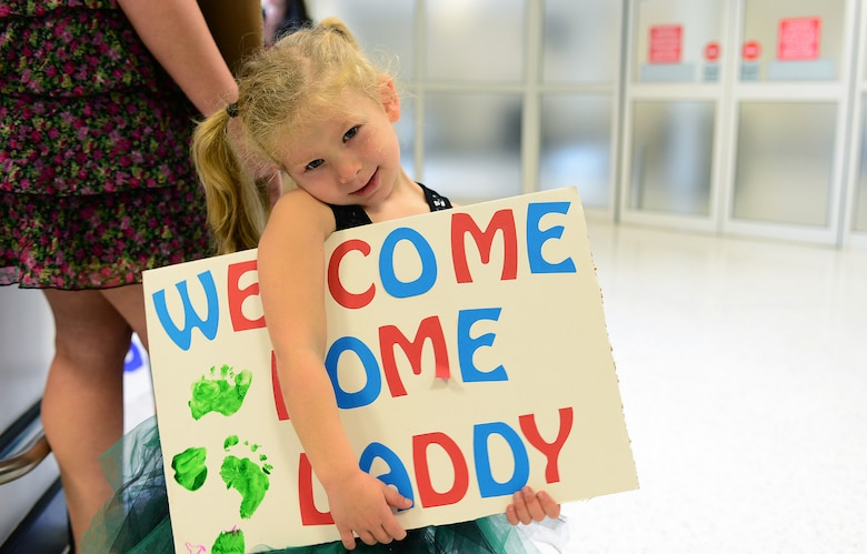 A young girl waits for her father at Royal Air Force Mildenhall, United Kingdom, Sept. 19, 2013, following his four- month deployment to Bagram Airfield, Afghanistan. Nearly 100 Airmen from the 56th Rescue Squadron and 748th Air Maintenance Squadron, stationed at RAF Lakenheath, U.K. returned this week. (U.S. Air Force photo/Airman 1st Class Dana J. Butler)