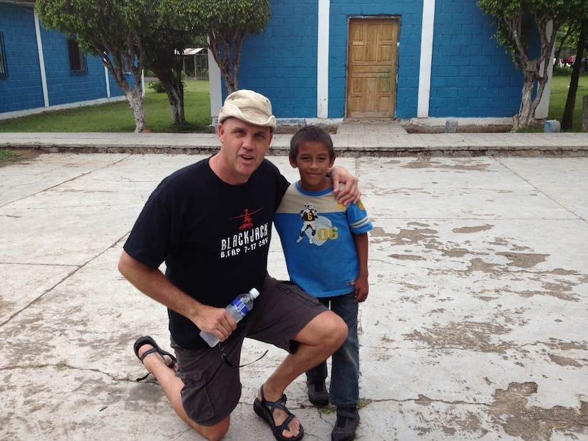 U.S. Army 1st Sgt. Robert Meek, 1-228th Aviation Regiment 1st Sgt, poses with an orphan while he and others visited San Antonio Padua Boy's home in La Paz, Honduras, Sept. 21, 2013. Members of 1-228th make regular visits to the boys' home to provide mentorship and food with the children.(Courtesy photo from members of 1-228th Aviation Regiment)