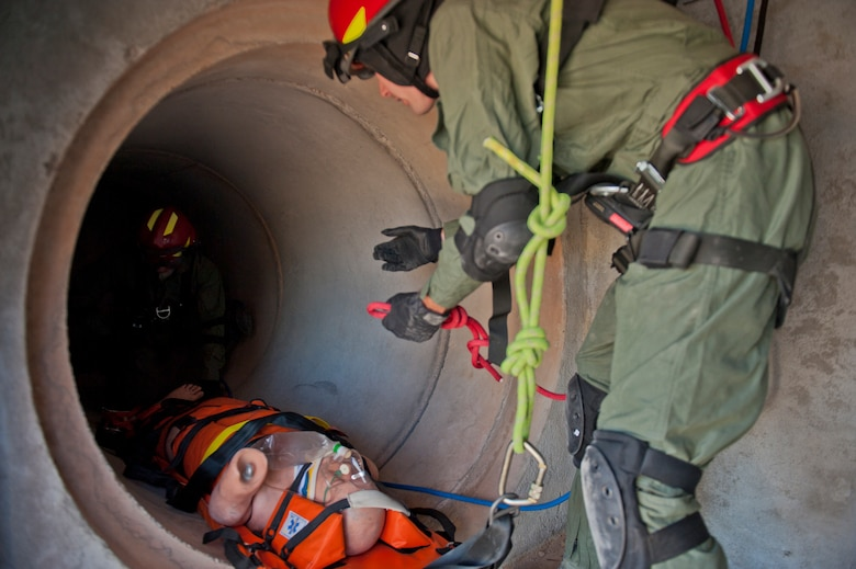 Senior Airman Tyler Clemons and SSgt. Justin Stacey, 49th Civil Engineering Squadron Fire Protection Flight firefighters, secure and retrieve a simulated casualty during a confined space training exercise at Holloman Air Force Base, N.M., Sept. 25. Firefighters from the 49th CES performed a series of training exercises during the 49th Wing's Unit Effectiveness Inspection Sept. 25 – 29. Holloman AFB is the first base in the Air Combat Command to undergo a UEI under the Air Force's new inspection system, announced in August. (U.S. Air Force photo by Airman 1st Class Aaron Montoya/Released)