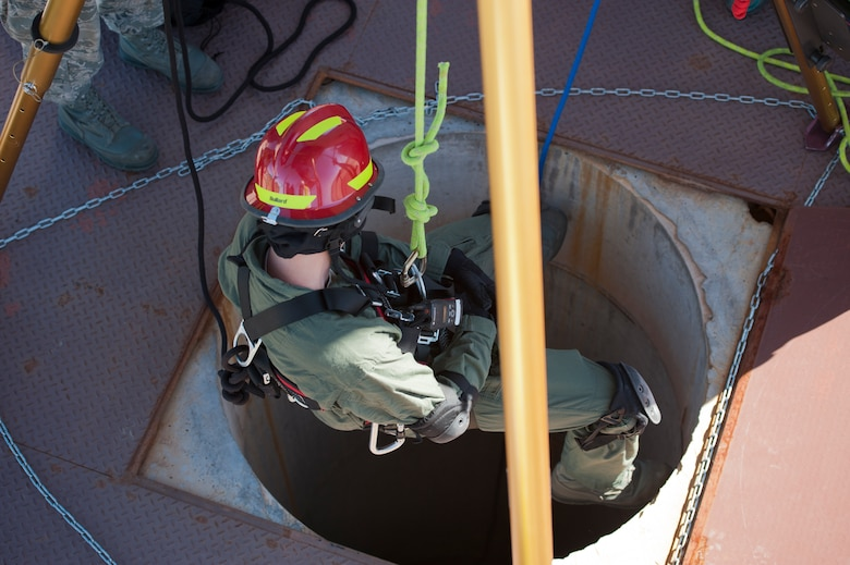 Staff Sgt. Justin Stacey, 49th Civil Engineering Squadron Fire Protection Flight firefighter, descends in to a space to secure and retrieve a simulated casualty during a confined space training exercise at Holloman Air Force Base, N.M., Sept. 25. Firefighters from the 49th CES performed a series of training exercises during the 49th Wing's Unit Effectiveness Inspection Sept. 25 – 29. Holloman AFB is the first base in the Air Combat Command to undergo a UEI under the Air Force's new inspection system, announced in August. (U.S. Air Force photo by Airman 1st Class Aaron Montoya/Released)