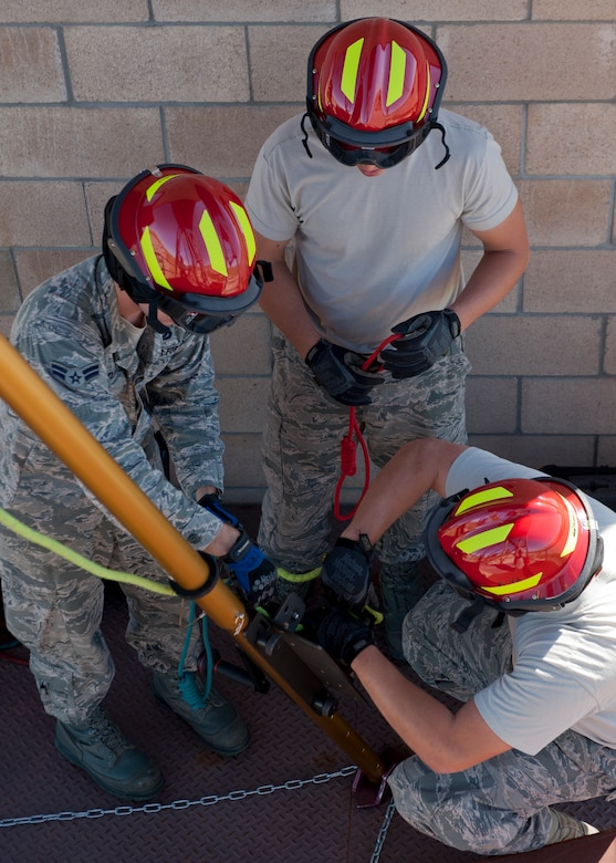 Airmen 1st Class Ryan Oke and John Murray and Senior Airman Gerrit Beernick, 49th Civil Engineering Squadron Fire Protection Flight firefighters, secure safety ropes to the rescue tripod during a confined space training exercise at Holloman Air Force Base, N.M., Sept. 25. Firefighters from the 49th CES performed a series of training exercises during the 49th Wing's Unit Effectiveness Inspection Sept. 25 – 29. Holloman AFB is the first base in the Air Combat Command to undergo a UEI under the Air Force's new inspection system, announced in August. (U.S. Air Force photo by Airman 1st Class Aaron Montoya/Released)
