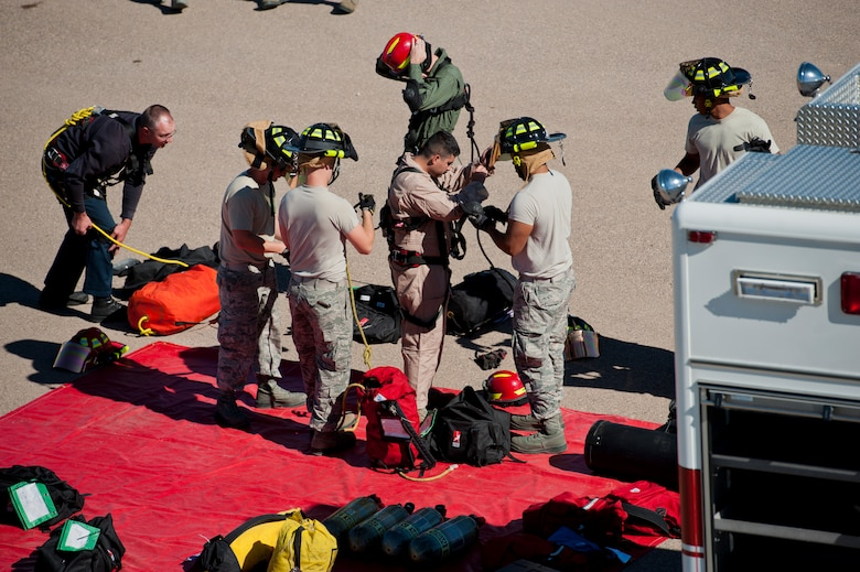 Members of the 49th Civil Engineering Squadron Fire Protection Flight don protective attire in preparation for a confined space training exercise at Holloman Air Force Base, N.M., Sept. 25. Firefighters from the 49th CES performed a series of training exercises during the 49th Wing's Unit Effectiveness Inspection Sept. 25 – 29. Holloman AFB is the first base in the Air Combat Command to undergo a UEI under the Air Force's new inspection system, announced in August. (U.S. Air Force photo by Airman 1st Class Aaron Montoya/Released)