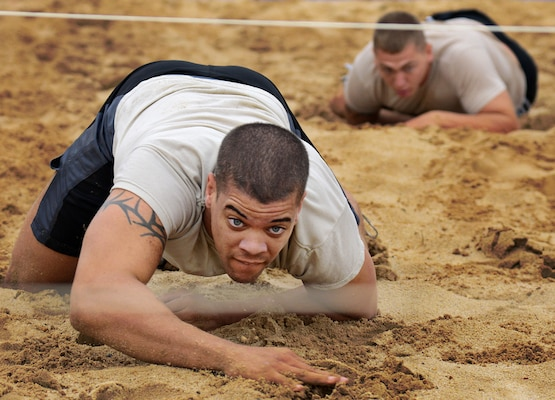 Members of team Wu-Tang, low crawl through the sand pit during the field exercises portion of the  Community Quest race September 18, at Joint Base San Antonio-Lackland. (U.S. Air Force photo by Benjamin Faske/released)