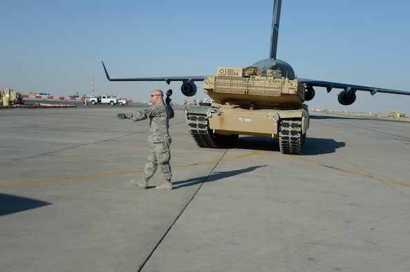 Master Sgt. Bradley Hayes, 386th Expeditionary Logistics Readiness Squadron ramp operations noncommissioned officer in charge, directs an M-1 tank following its offload at an undisclosed location in Southwest Asia, Sept. 26, 2013.  Ramp personnel at the 386th Air Expeditionary Wing on average handle more than 3,000 tons of cargo each month.  (U.S. Air Force photo by Master Sgt. Chris Campbell)