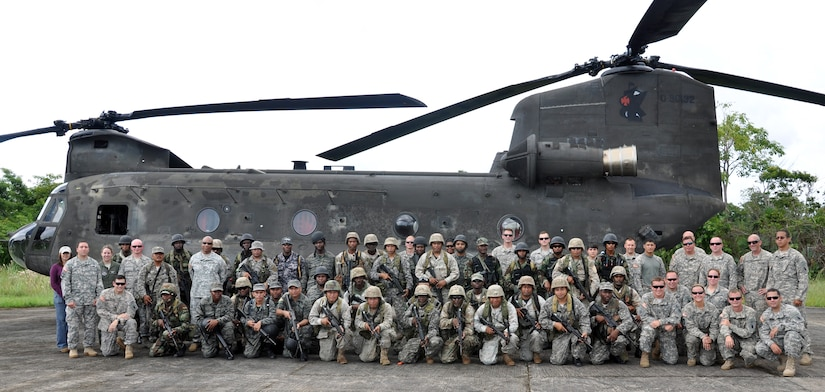 Members of Joint Task Force-Bravo and members of the Belizean armed forces pose in front of one of Joint Task Force-Bravo's CH-47 Chinook helicopter's prior to a training exercise in Belize, Sept. 26, 2013.  Joint Task Force-Bravo and the Belizean military performed joint military training in order to enhance operational capabilities as well as to continue to build international relationships.  (U.S. Air Force photo by Capt. Zach Anderson)