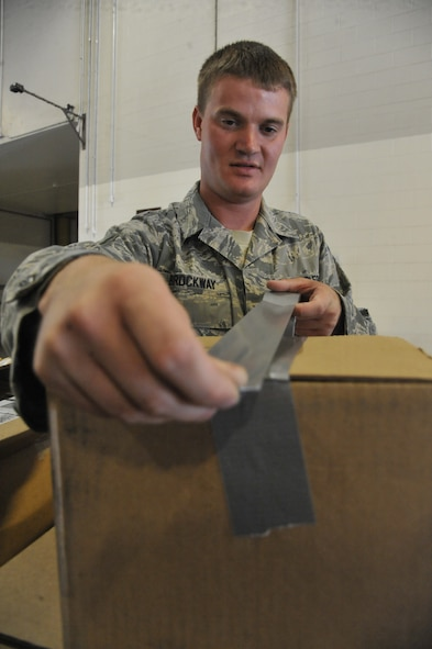 U.S. Air Force Staff Sgt. Chris Brockway, 442nd Logistics Readiness Squadron traffic management apprentice, tapes a package at Whiteman Air Force Base, Mo., Sept. 23, 2013. All packages must be secured and delivered to the customer in a timely manner. (U.S. Air Force photo by Airman 1st Class Keenan Berry/Released)