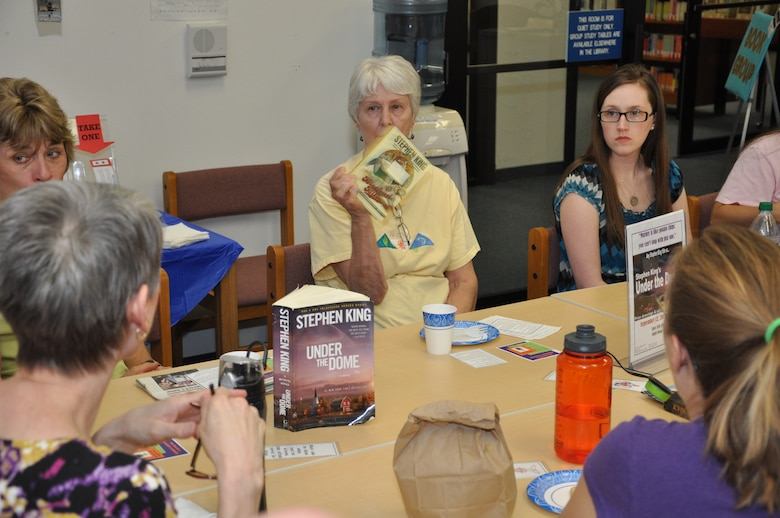 Carol Cop, former Luke library technician, holds up her copy of a Stephen King novel during the book club for adults discussion at the library Sept. 12. The group selected this month to read any novel written by author Stephen King. (U.S. Air Force photo/Staff Sgt. Luther Mitchell)