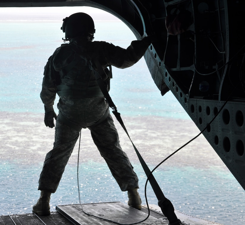A crewchief takes in the view of a corral reef off the coast of Honduras from the ramp of a CH-47 Chinook helicopter, Sept. 28, 2013. The Chinook was transporting members of Joint Task Force-Bravo's Central America Survey and Assessment team back to Soto Cano Air Base following an exercise operation in Belize. (U.S. Air Force photo by Capt. Zach Anderson)