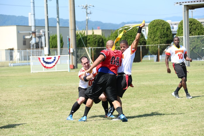 Lance Cpl. Anthony Raymond, Headquarters and Headquarters Squadron armory specialist, rips away the flag from Staff Sgt. Mike Rodriguez, Marine Aircraft Group 12 fiscal chief and center, during the flag football Fall Classic at Penny Lake fields aboard Marine Corps Air Station Iwakuni, Japan, Sept. 20, 2013. This is the third consecutive year H&HS has won the Fall Classic.