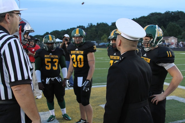 U.S. Marine Corps Maj. Gabriel Diana, the Commanding Officer of Recruiting Station Charleston and Columbus, Ohio native, tosses a coin to determine who will kick or receive during a high school football game between Cabell Midland and Huntington at Cabell Midland High School Sept. 20, 2013. Several members of the Cabell Midland football team have enlisted in the Marine Corps, and one of those, defensive end Rian Caudill, is the son of  U.S Marine Corps Master Sgt. Will Caudill, RS Charleston operations chief and native of Charleston, W.Va.