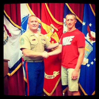 U.S. Marine Corps Master Sgt. Will Caudill, the Operations Chief of Recruiting Station Charleston and native of Charleston, W.Va., congratulates his son Rian after enlisting in the Marine Corps July 9, 2013. Rian, a 17-year-old senior at Cabell Midland and defensive end for the football team, is one of three members of the football team who recently enlisted in the Marine Corps. (Courtesy Photo)