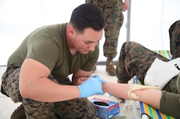 Petty Officer 2nd Class Jonathan Sosa finds a vein as he practices intravenous access skills at Clark Air Field, Pampanga, Republic of the Philippines, Sept. 21 as part of Amphibious Landing Exercise 2014. The afternoon of training allowed the corpsmen to refresh their skills as well as prepare for any humanitarian assistance mission that could occur within the Asia-Pacific Region. PHIBLEX 14 is an annual Philippine-U.S. training exercise that enhances stability and security within the region while also preparing both forces for humanitarian assistance and disaster relief. Sosa is a hospital corpsman with Combat Logistics Battalion 13, 13th Marine Expeditionary Unit. (Marine Corps photo by Lance Cpl. Anne K. Henry/RELEASED)