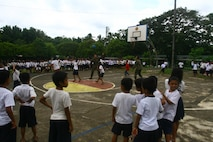 Petty Officers 2nd Class Neil C. Domingo, left, Kahealani W. Aipia play basketball with students from Taysan Elementary School September 23 at the school in Legazpi City, Albay, Republic of the Philippines, as part of Amphibious Landing Exercise 2014. The civil-military component of PHIBLEX 14 promotes engineer and medical operational readiness while providing services to areas where there is an identified need for engineering improvements and medical care. Aipia and Domingo are hospital corpsmen with 3rd Medical Battalion, 3rd Marine Logistics Group, III Marine Expeditionary Force. (U.S. Marine Corps photo by Sgt. Brian A. Marion/Released)