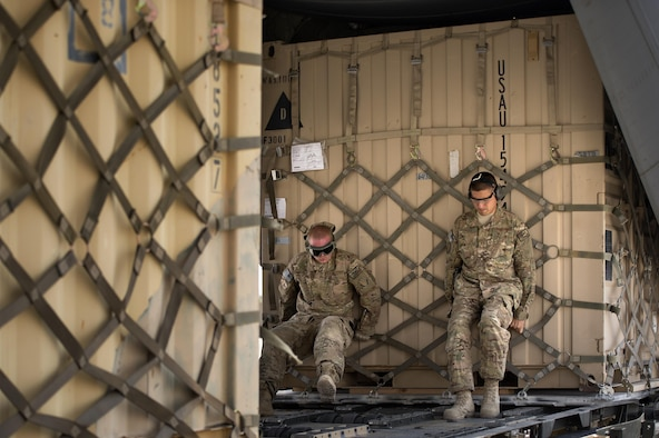 "Senior Airman Matthew Hunter and Tech. Sgt. Jonnedi Paule, 19th Movement Control Team aerial porters, heft a ""tricon"" shipping container into a C-130 Hercules cargo plane at Forward Operating Base Salerno, Khost province, Afghanistan, Sept. 21, 2013. The 19th MCT, a small squadron of Air Force surface movement controllers and aerial porters, have the herculean task of overseeing the vast majority of retrograde operations at FOB Salerno. Hunter and Paule are both forward deployed from Travis Air Force Base, Calif."