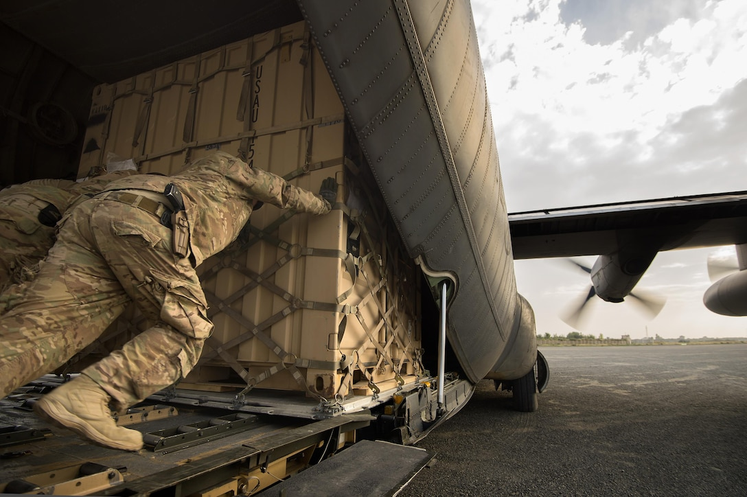 """Staff Sgt. Daniel Hall, along with other 19th Movement Control Team aerial porters muscle a """"tricon"""" shipping container into a 774th Expeditionary Airlift Squadron C-130 Hercules cargo plane at Forward Operating Base Salerno, Khost province, Afghanistan, Sept. 22, 2013."""