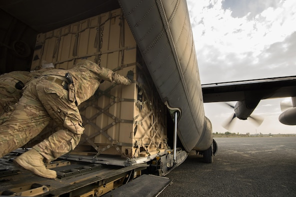 "Staff Sgt. Daniel Hall, along with other 19th Movement Control Team aerial porters muscle a ""tricon"" shipping container into a 774th Expeditionary Airlift Squadron C-130 Hercules cargo plane at Forward Operating Base Salerno, Khost province, Afghanistan, Sept. 22, 2013."