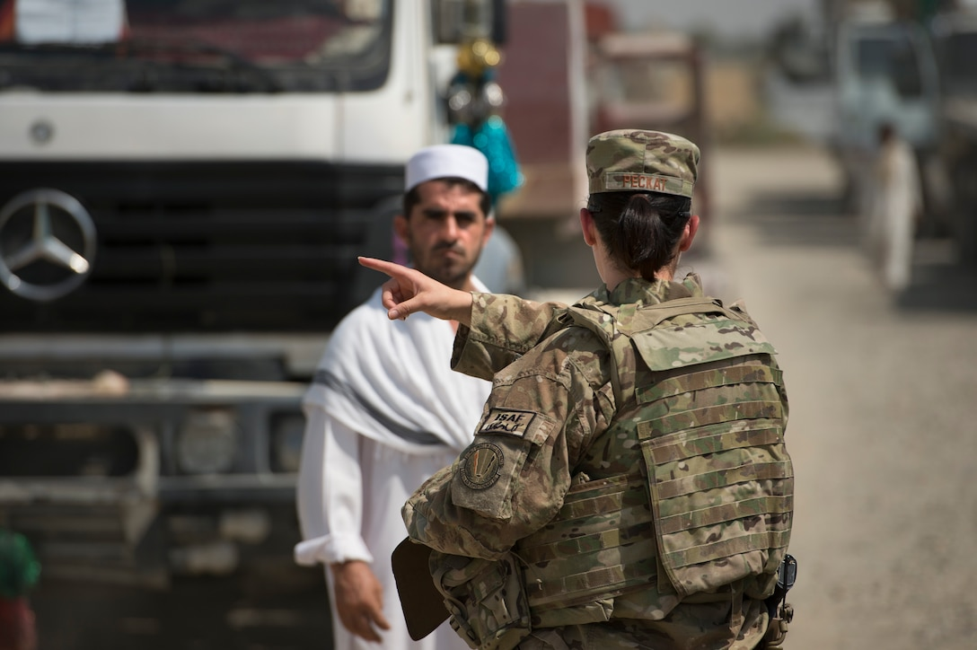 Tech. Sgt. Christina Peckat, 19th Movement Control Team surface movement Airman, coordinates trucker traffic with Abdul Basir, a parking attendant, at Forward Operating Base Salerno, Khost province, Afghanistan, Sept. 22, 2013. The 19th MCT, a small squadron of Air Force surface movement controllers and aerial porters, have the herculean task of overseeing the vast majority of retrograde operations at FOB Salerno. Peckat, a Denver, Colo. native, is deployed from RAF Mildenhall, England.