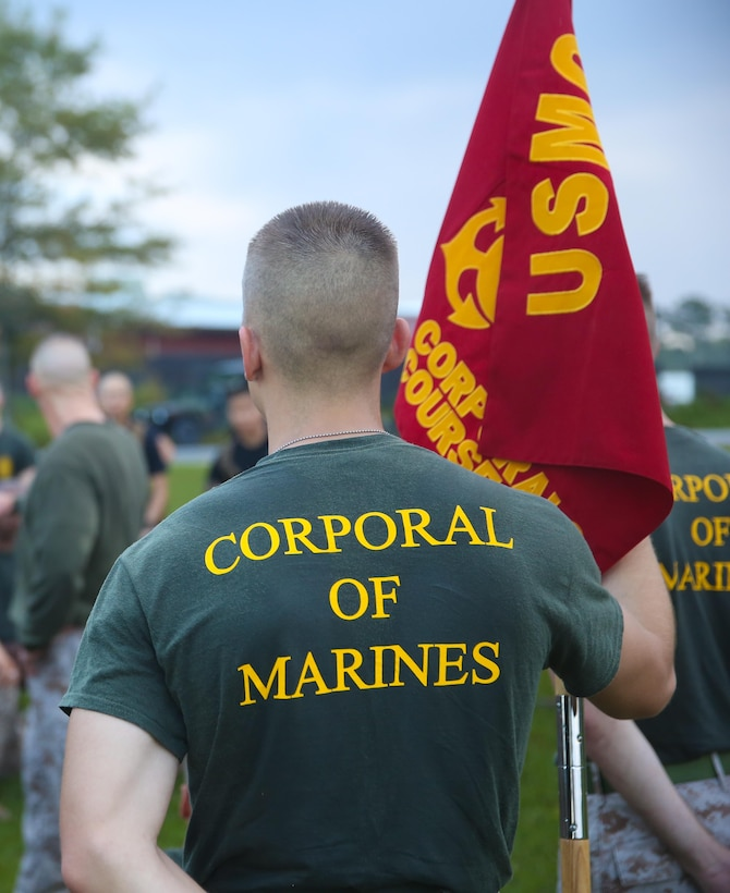Corporal Trevor L. Jones, an amphibious assault vehicle crewman with 2nd Assault Amphibian Battalion, 2nd Marine Division, holds the guide-on after the corporal's course motivational hike Sept. 26, 2013 aboard Marine Corps Base Camp Lejeune. A total of 54 corporals started the course and graduated Sept. 27, 2013.