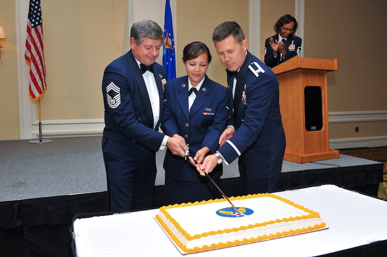 """Retired Chief Master Sgt. of the Air Force David J. Campanale, left; Airman Amanda Belarde, 460th Space Wing Legal Office military justice paralegal, center; and Col. Dan Wright, 460th SW commander, cut the Air Force birthday cake during the Air Force Ball Sept. 27, 2013, at the Renaissance Hotel in Denver. This year's celebration marked the 66th Air Force birthday and paid respects to 1st Lt. John Harold """"Buck"""" Buckley the base's namesake, who was killed during World War I 95 years ago. (U.S. Air Force photo by Senior Airman Phillip Houk/Released)"""