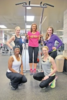 From left, front row, Traci Scott, regional liaison officer, 1st Inf. Div., and Rachel Gilmore, military spouse; and back row, Kelsey Ellis, military spouse, Angi Buckley, personal trainer, and Ashley Wiggins, military spouse, pose for a photo after a March 22 training session at King Field House. The women have found a supportive community of female body builders at Fort Riley.