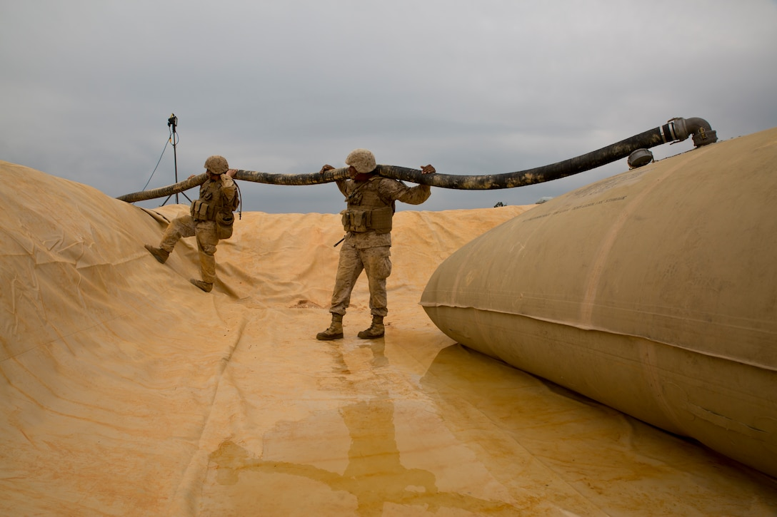 Lance Cpls. Raymond P. Sanborn, left, and Quawe M. Morgan hold up a 4-by-50 suction hose at Landing Zone Falcon in the Central Training Area March 27 during a field training exercise. Elevating the hose removes possible kinks in the fuel line and allows fuel to flow more efficiently into the storage bladder. Sanborn and Morgan are bulk fuel specialists with Bulk Fuel Company, 9th Engineer Support Battalion, 3rd Marine Logistics Group, III Marine Expeditionary Force.