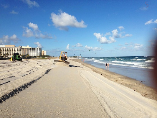 Workers flatten delivered sand on a Broward County beach so it fills an engineer-designed template, which includes the sand placement's height and width along the beach.