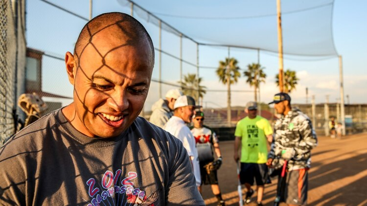 Petty Officer 2nd Class Gabriel Cisneros, religious program specialist, 15th Marine Expeditionary Unit, jokes with teammates after softball practice aboard Camp Pendleton, Calif., March 13, 2014. Cisneros, 36, is from Diamond Bar, Calif.  (U.S. Marine Corps video by Cpl. Emmanuel Ramos/Released)