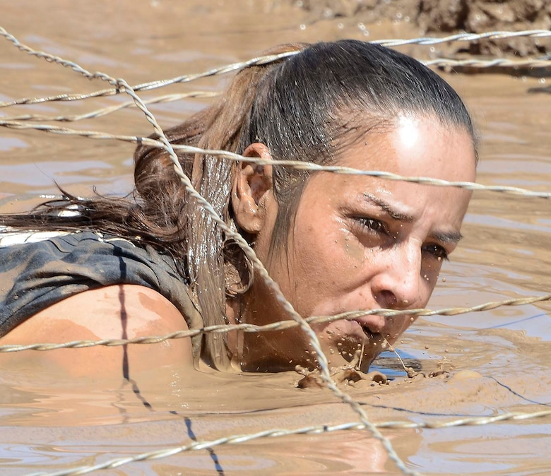 Master Sgt. Larita Trudell, 12th Air Force (Air Forces Southern) Commander Support Staff Superintendent, crawls underneath wires through muddy water during a portion of the Hard Charge Televised Obstacle Mission at the Pima County Fairgrounds in Tucson, Ariz., on March 29. The team of 11 members completed the four mile course with of obstacles designed to utilize a mix of strength, stamina, balance, and body awareness  that pushed participants to both mental and physical fatigue. (U.S. Air Force photo by Staff Sgt. Adam Grant/Released)