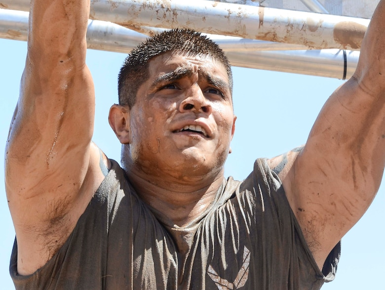 Staff Sgt. Fernando Diaz III, 12th Air Force (Air Forces Southern) Client Systems Technician, prepares to begin the monkey bars during a portion of the Hard Charge Televised Obstacle Mission at the Pima County Fairgrounds in Tucson, Ariz., on March 29. Climbing, crawling and sprinting were a few of the many ways the members form 12th AF maneuvered though the rigorous four-mile 37-obstacle course. (U.S. Air Force photo by Staff Sgt. Adam Grant/Released)